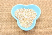Barley groats in blue bowl on jute canvas — Stock Photo