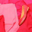 Heap of red and pink clothes with womanly shoes — Stock Photo #51793535