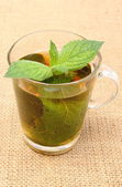 Fresh green mint in cup of beverage on burlap texture — Foto de Stock