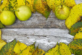 Leaves and pear on a wooden background — Stock Photo