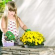 Little girl planting flowers in pots — Stock Photo #49052887