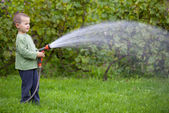 Boy watering the grass — Stock Photo