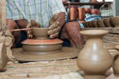 A man shapes pottery as it turns on a wheel — Foto Stock