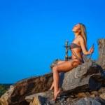 Girl dressed in a bikini smokes a hookah on a hillside — Stock Photo #49832211