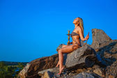Girl dressed in a bikini smokes a hookah on a hillside — Stock Photo