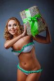 Curly-headed girl in bikini with gift — Stock Photo