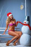 Girl in a pink bikini with a snowman — Photo