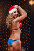 Backside of a curly-headed girl in a bikini and red hat — Stock Photo