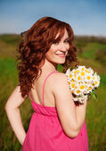 Candid carefree adorable woman in field with flowers — Stock Photo