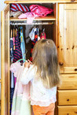 Cute little girl hanging up her clothes — Stock Photo