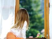 Cute little girl sitting on a bathroom window — Stockfoto