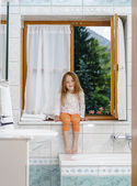 Cute little girl sitting on a bathroom window — Stok fotoğraf