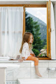 Cute little girl sitting on a bathroom window — Stockfoto