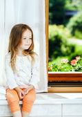 Cute little girl sitting on a bathroom window — Stock Photo