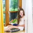 Cute teenage girl siiting on window siil — Stock Photo #48948773