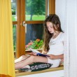 Cute teenage girl siiting on window siil — Stock Photo #48948783