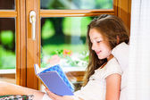 Cute teenage girl siiting on window siil  — Stock Photo