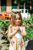 Cute little girl with flowers chaplet — Stock Photo
