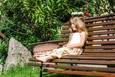 Cute litle barefoot girl sitting on the bench — Stock Photo
