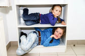 Two sisters fitting in storage rack — Stock Photo