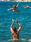 Father throwing baby over the water — Stock fotografie