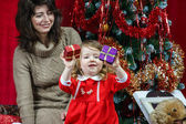 Mother with little daughter finding christmas gifts — Foto Stock