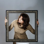 Young woman lean out from picture frame — Stock Photo