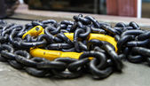 Black metal chain with yellow hook — Foto Stock