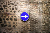 Classical road sign on ancient wall — Stockfoto
