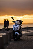 Lonely scooter on sunset background — Stockfoto