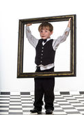 Freckled red-hair little boy with big picture frame. — Stock Photo