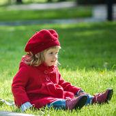 Schattig klein meisje op het groene gras — Stockfoto