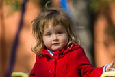 Surprising little girl dressing in red coat — Stock Photo