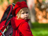 Cute little girl dressing in red coat — Stock Photo
