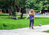 Cute little girl frighting pigeons — Stock Photo