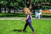 Niña linda caminando sobre la hierba verde — Foto de Stock