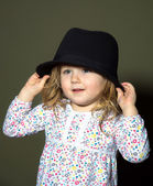 Cute little girl playing with hat — Stock Photo