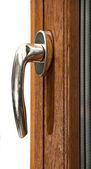 Gold window handle on oak laminated fiberglass window — Stock Photo