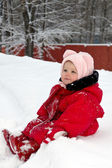 Cute adorable baby sitting on snow in winter park — Stock Photo