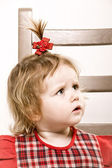 Cute little girl in red dress sitting on a chair — Stock Photo