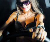 Sexy glamour girl sitting in a car — Stock Photo