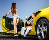 Пара любовников и желтый спортивный автомобиль — Стоковое фото
