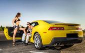 Casal de amantes e carro esporte amarelo — Fotografia Stock