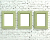 Three frames on white brick wall — Stock Photo
