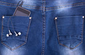 MP3 player and earphones sticking out of jeans pocket — Foto de Stock