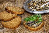 Rye bread with delicious anchovies on old wooden table — Stock Photo