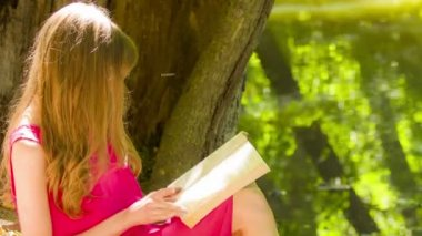 Beautiful young brunette woman reading a book — Stock video