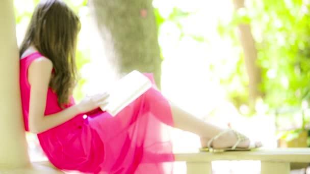 Hermosa joven morena leyendo un libro — Vídeo de stock