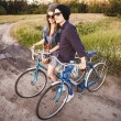 Two beautiful hipsters standing outdoor in summer with white vintage fixed gear bicycle — Stock Photo #49276611