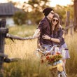 Two beautiful hipsters standing outdoor in summer with white vintage fixed gear bicycle — Stock Photo #49276613